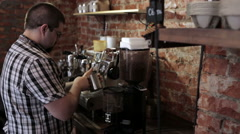 The guy barista with a beard and glasses whips milk - stock footage