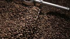 Batch of freshly roasted coffee beans cooling after emerging from a roaster Stock Footage