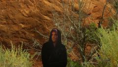 Hooded person walking out bushes creepy satanic Stock Footage