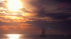 A tall clipper ship sails at sunset. - stock footage