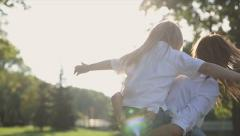 Family values: Mother take into arms daughter and spin around at sunset. Slo mo - stock footage
