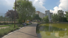 WSitting on a bench on the waterfront, in Iulius Park, Cluj-Napoca Stock Footage