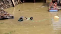 Asian workers dive up rubble from the bottom of a muddy lake 4k Stock Footage