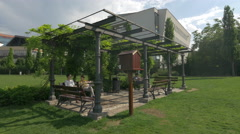 WYoung people relaxing under a steel pavilion in Iulius Park, Cluj-Napoca Stock Footage