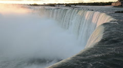 First ray of morning sunlight touches the falling water of Niagara Falls Stock Footage