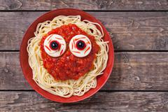 Scary halloween food pasta with big red eyes. Monster face for celebration party - stock photo
