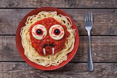 Halloween scary pasta food vampire face with big eyes and moustaches in red dish - stock photo