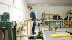 4K Professional carpenter in workshop, processing timber on industrial machine Stock Footage