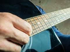 Closeup photo of an acoustic guitar played by a man Stock Photos