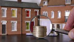 Model houses with sterling (pounds) being magnified. - stock footage
