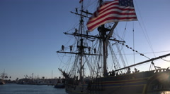 Sailors stand on the mast of a tall historic clipper ship as it sails on the Stock Footage