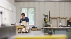 4K Furniture maker in workshop, having a hot drink while he works on his designs Stock Footage