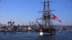 Sailors stand on the mast of a tall historic clipper ship as it sails in the Stock Footage