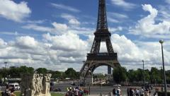 Tilting down from Eiffel Tower to the ground with sunny day backdrop - stock footage