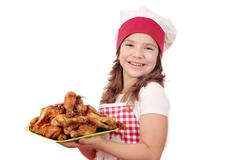 happy little girl cook with chicken drumstick on plate - stock photo