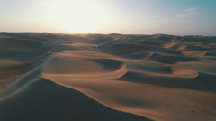 flying over sand dunes at dusk with long shadows on the sand - stock footage