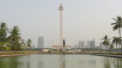Monas Monument with birds flying over pond,Jakarta,Java,Indonesia Stock Footage