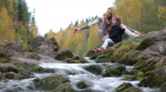 A young mother and her cute daughter sitting near the forest stream. Stock Footage