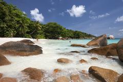 Granite cliffs and beach at Anse Lazio turquoise sea Praslin Island Seychelles - stock photo