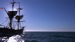 A tall masted clipper ship sails on the high seas against the sun. - stock footage