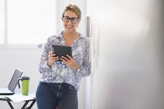 Stock Photo of Young woman working in office