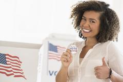 Stock Photo of Young woman holding voting badge and smiling