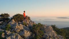 Aerial - Around young man standing on seaside mountain Stock Footage