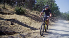 Man riding mountain bike on dirt road Stock Footage