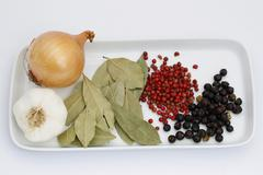Onion garlic bay leaves red and black peppercorns - stock photo