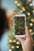 Personal perspective of person photographing Christmas tree - stock photo