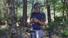 Mountain biker takes a break to check cell phone - stock footage