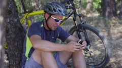 Man with mountain bike sits down taking break and checking cell phone - stock footage