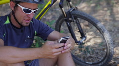 Closeup of of Mountain biker talking on cell phone - stock footage