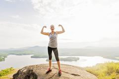 Stock Photo of Young woman standing on top of mountain and flexing muscles