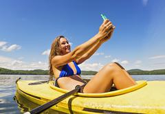 Stock Photo of Young woman taking selfie in kayak on lake