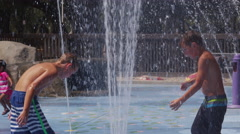 Children playing in water fountains on summer day, slow motion - stock footage