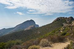 Trail with Genoese tower behind coastal and mountain scenery Gulf of Porto Stock Photos