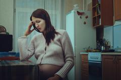 Stock Photo of Sad pregnant woman sitting in the kitchen.