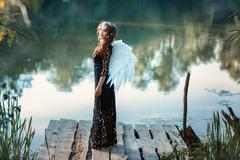 Girl with angel wings standing on the pier and smiling. - stock photo