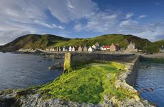 Coastline with green algae on the Crovie Pier and large stones fishing area Stock Photos