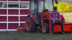 Farmer sits on tractor using laptop computer - stock footage