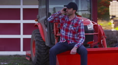 Farmer sits on tractor using cell phone - stock footage