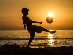 Boy with soccer ball sunset at the sea beach Italy Europe - stock photo