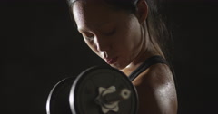 Active Asian woman lifting dumbbells weights and sweating Stock Footage