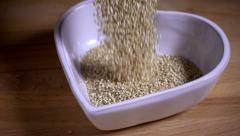 Quinoa seeds falling into heart shaped bowl, slow motion Stock Footage