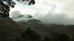 Clouds rolling across snowy mountain peaks Stock Footage