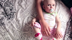 Stock Video Footage of Eight month baby girl lies on the bed