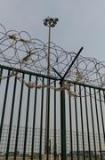 Green fence with razor wire and floodlights guarding French ferry terminal. - stock photo