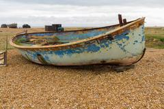Old derelict boat on pebble beach. - stock photo
