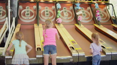 Three little girls playing skee ball Stock Footage